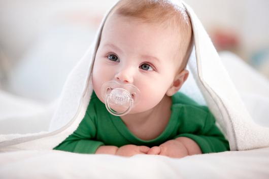 маленький ребенок лежа сосет пустышку