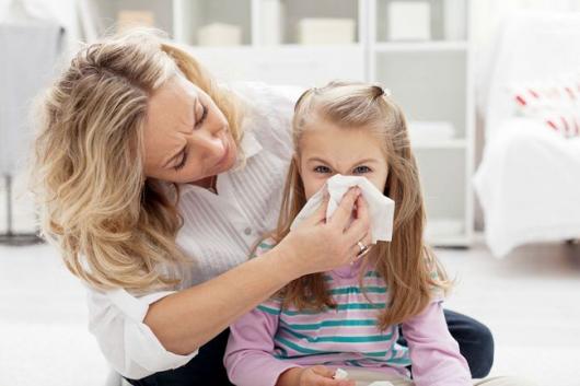 Мама помогает дочке высмаркать нос