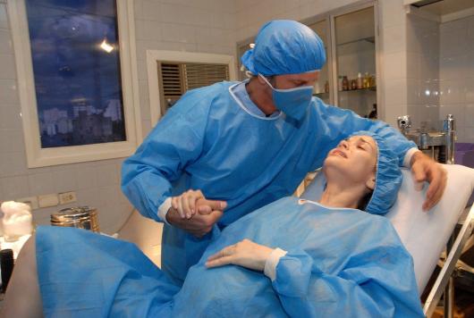 мужчина успокаивает жену во время родов