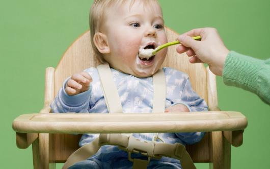 ребенка в стульчике кормят с ложечки
