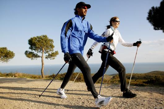 парень с девушкой занимаются скандинавской ходьбой