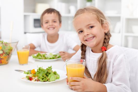 девочка и мальчик пьют сок и едят салат