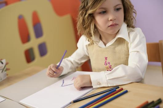 ребенок рисует цветными карандашами