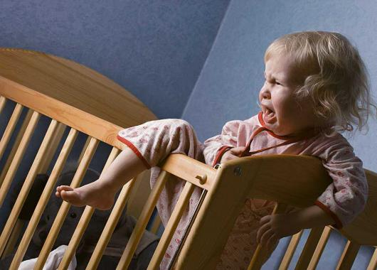 девочка пытается вылезти из кровати
