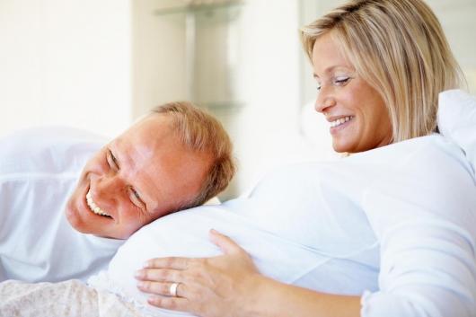 муж слушает живот беременной жены