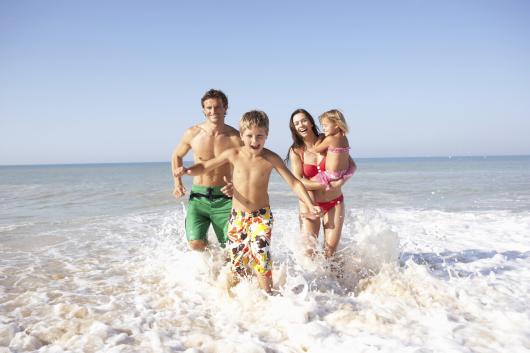 семья с детьми бежит по берегу моря