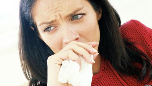 девушка закрывает рот платком