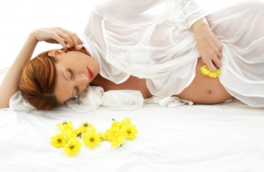 беременная гладит живот лепестками цветов