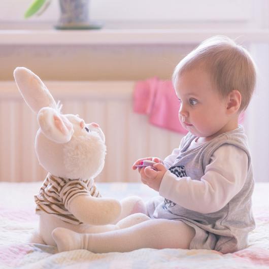 ребенок играет с зайкой