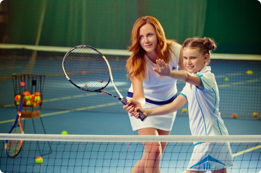 ребенок занимается теннисом с тренером