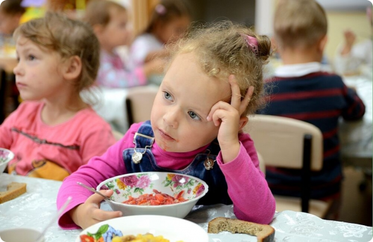 девочка в детском садике кушает суп