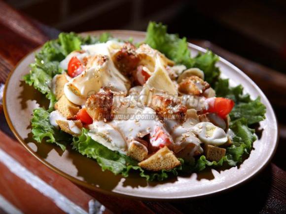 салат с курицей и сухариками на листьях салата