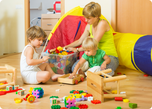 мама с детьми убирает игрушки в комнате